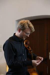 Julian Steckel beim Aufziehen der neuen Saite, Foto: Karlheinz Krämer