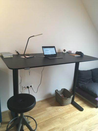 Ein Schreibtisch im Homeoffice mit einem aufgeklappten Notebook unter einer Schreibtischlampe, davor ein Hocker